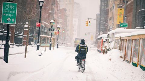 """Neben einem grünen Hinweisschild mit weißer """"Manhattan Bridge""""-Schrift fährt ein Radfahrer durch eine tief verschneite Straße"""