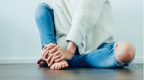 Frau umfasst Fuß mit Händen