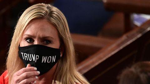 """Eine blonde, mittelalte Frau in rotem Oberteil fasst an ihren schwarzen Mund-Nasen-Schutz mit weißem """"Trump won""""-Schriftzug"""