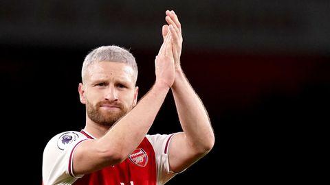 Shkodran Mustafi steht im rot-weißen Trikot des FC Arsenal vor einem schwarzen Nachthimmel und applaudiert auf Kopfhöhe