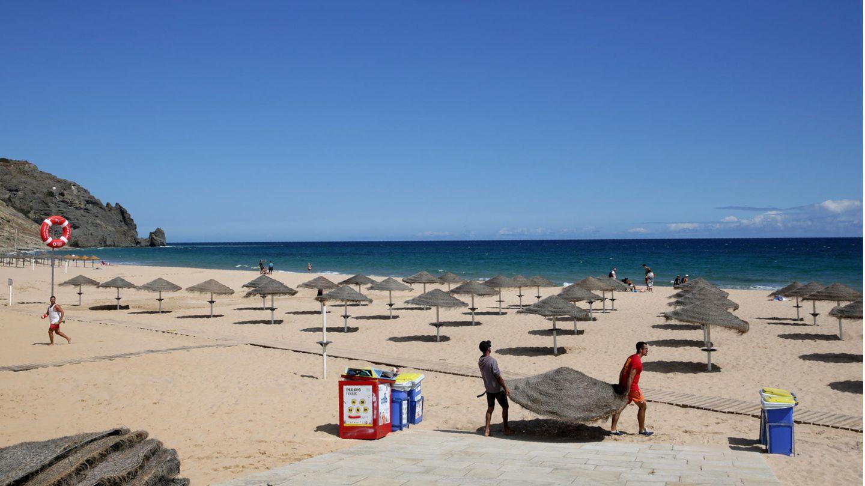 An der Praia Da Luz: Zwei Männer räumen am Strand derportugiesischen Algarveküstedie Sonnenschirme ab.