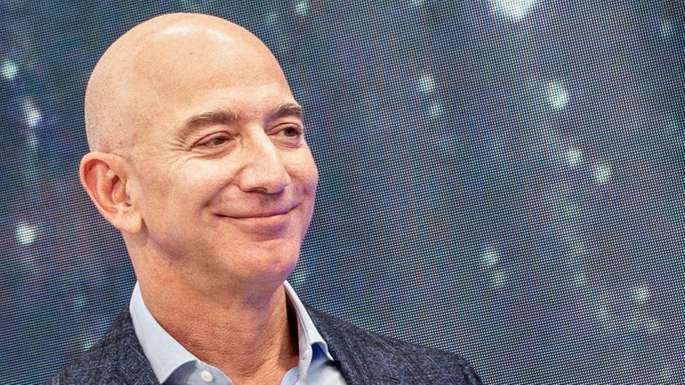 Jeff Bezos - ein kahlköpfiger weißer Mann - steht lächelnd auf einer Bühne. Hinter ihm zeigt Riesenbildschirm ihn