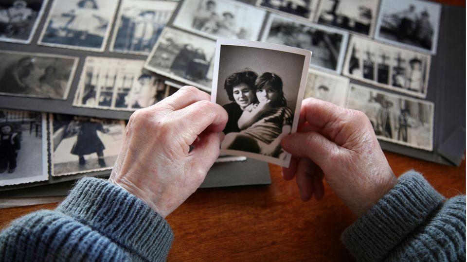 Altenpflege: Eine ältere Frau sieht sich alte Fotos an