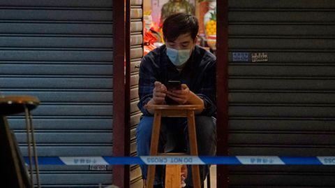 Ein Mann vertreibt sich die Zeitmit seinem Smartphone, während er auf sein Corona-Testergebnis wartet.Bewohner im gesperrten Bereich des Honkonger Bezirks Sham Shui Po sind verpflichtet, über Nacht zu Hause zu bleiben, bis sie einen negativen Corona-Test vorweisen können.