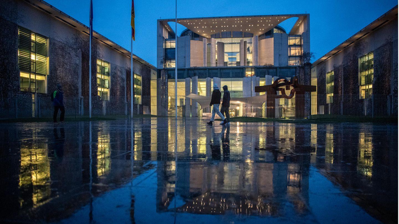 Berlin: Fußgänger laufen im Regen am Bundeskanzleramt vorbei. Dort tagte am Abend der Koalitionsausschuss.