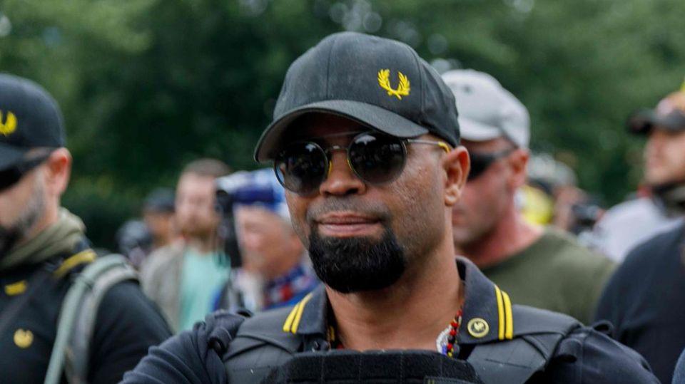 Un hombre con una gorra de béisbol negra, gafas de sol y un polo negro con una cinta amarilla en el cuello se encuentra frente a una manifestación.