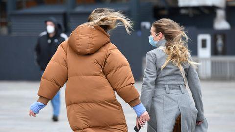 Passanten gehen in Köln über die windige Domplatte
