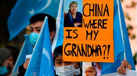 """Ein junger Uiguren-Aktivist hält ein Plakat hoch:""""China wo ist meine Oma?!"""""""