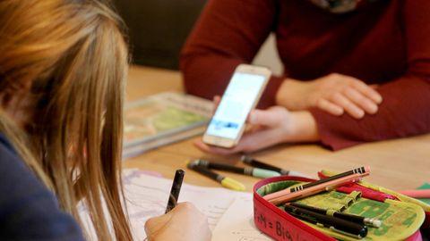 Eine Frau hält einem Mädchen, das in ein Schreibheft schreibt, das erleuchtete Display eines Smartphones hin