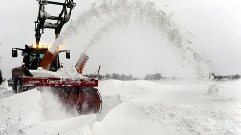Eine Schneefräse räumt auf Fehmarn eine Straße von Schneewehen frei