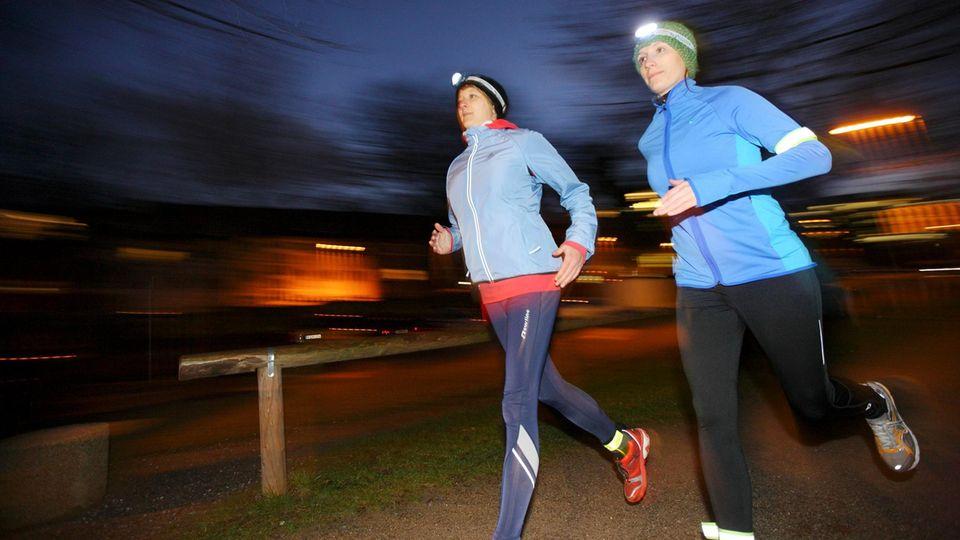 Joggen im Dunkeln: Zwei Läuferinnen mit Stirnlampe in der Dämmerung