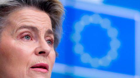 Das Gesicht von Ursula von der Leyen in Großaufnahme mit einer unscharfen EU-Flagge im Hintergrund