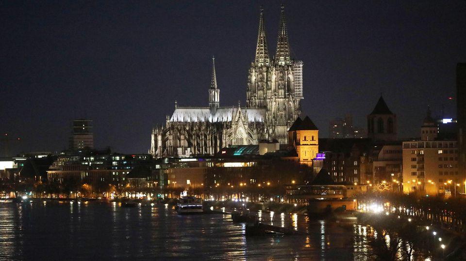 Das Rheinufer in Köln mit dem Dom am Freitagmorgen bei Dunkelheit