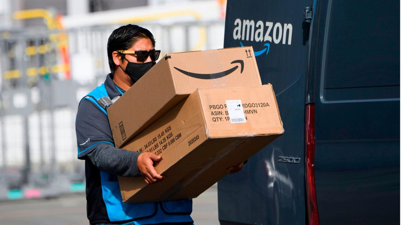 Ein Amazon-Fahrer trägt Pakete