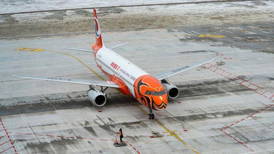 Landung des als Vogel Phönix lackierten Airbus A320 von Chongqing Airlines, eine Tochterfirma der großen China Southern Airlines, als erster Linienflug überhaupt auf dem kurz vor Weihnachten 2020 eröffneten neuen Xiannyushan Airport.