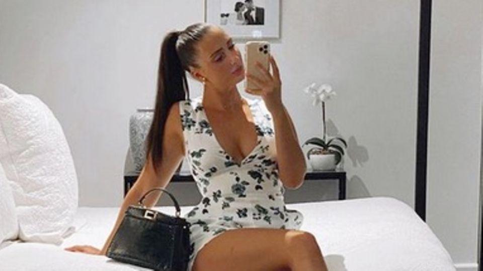 Model Isabelle Eleanore sitzt auf einem Bett und macht ein Selfie von sich