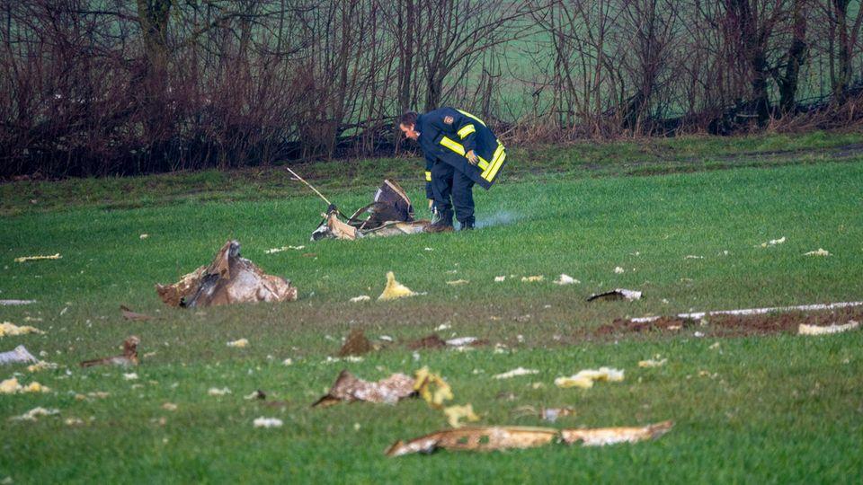 Ein Polizist markiert den Bereich der Trümmerteile nach dem Absturz eines Kleinflugzeugs.
