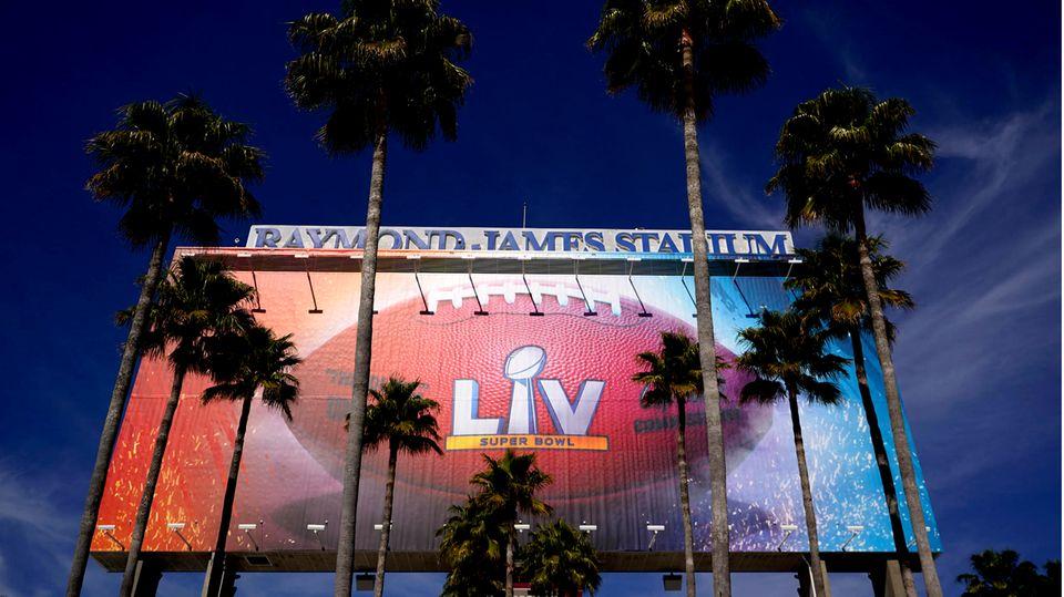 USA, Tampa: Ein Schild für den Superbowl 55 wird von Palmen am Raymond James Stadium eingerahmt