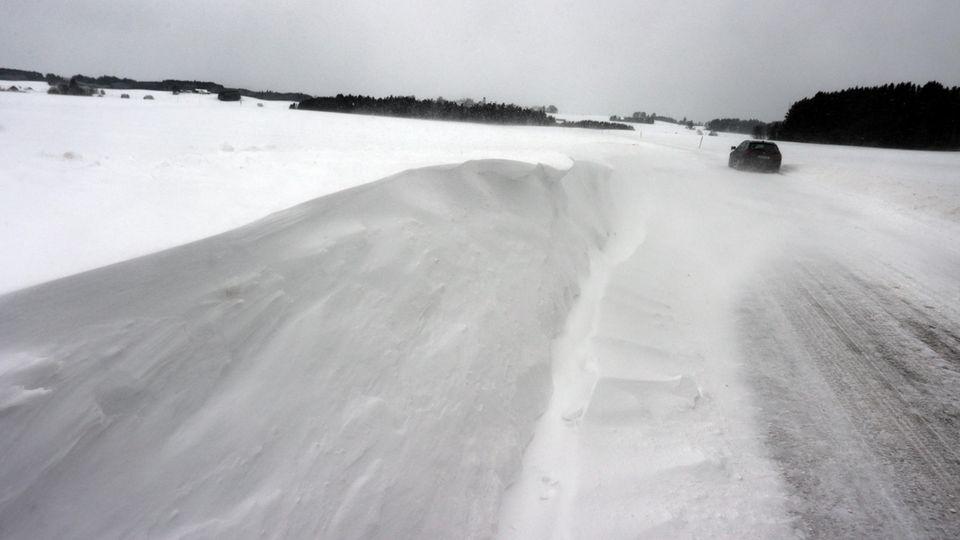 Ein Auto fährt über eine von Schneeverwehungen bedeckte Landstraße