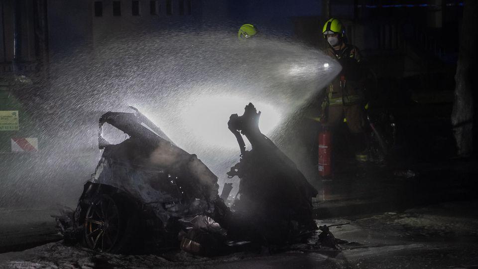 Einsatzkräfte der Feuerwehr löschen am Treptower Park ein Autowrack.
