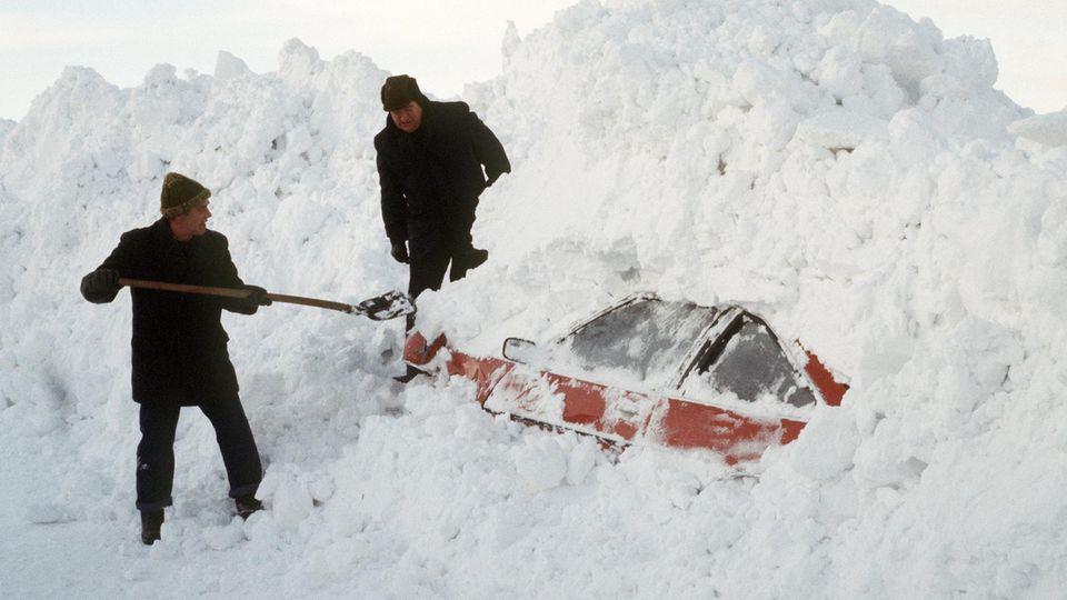 Winter 1979: Zwei Männer graben in Schleswig-Holstein mit einer Schaufel ein Auto aus den Schneemassen