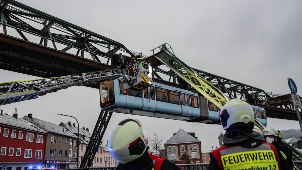 Einsatzkräfte der Feuerwehr befreien mit einer Drehleiter Fahrgäste aus einem Wagen der Schwebebahn