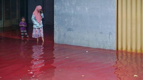 In einer indonesischen Stadt liefen die Anwohner durch rotgefärbtes Wasser, das die Straßen überflutet hatte