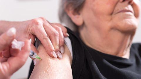 Eine Rentnerin erhält eine Spritze in den Oberarm