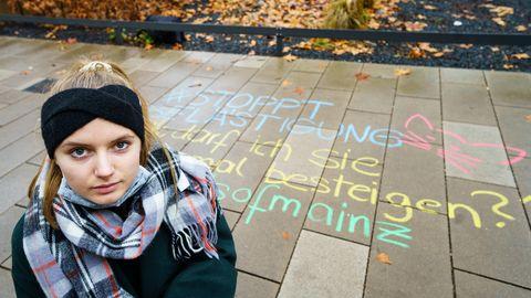 Melina Crispin, Aktivistin, kniet vor einem in Kreide aufgeschriebenem anzüglichen Kommentar