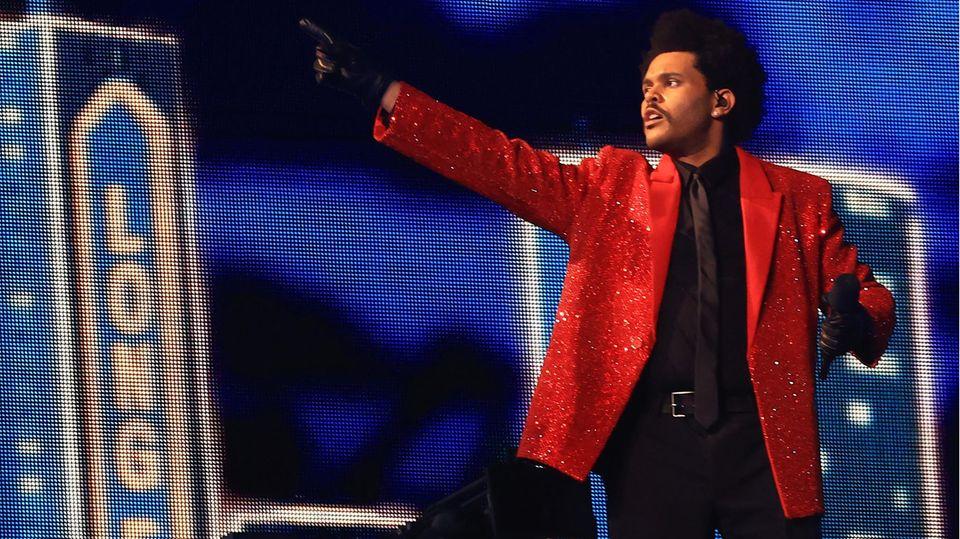 In einem roten Jackett steht The Weeknd vor einer eindrucksvollen Kulisse. 7 Millionen Dollar (5,3 Millionen Euro) aus eigener Tasche hat der Sänger bezahlt, um das Spektakel perfekt zu machen. Für ihn wurde eigens eine Tribüne gebaut, die wie eine Theaterbühne funktionierte.