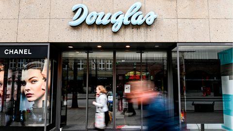 Passanten laufen vor dem geschlossenen Eingang eines Kaufhauses der Parfümerie-Filialkette Douglas in Hamburg