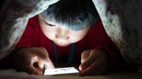 Kind unter einer Decke am Smartphone