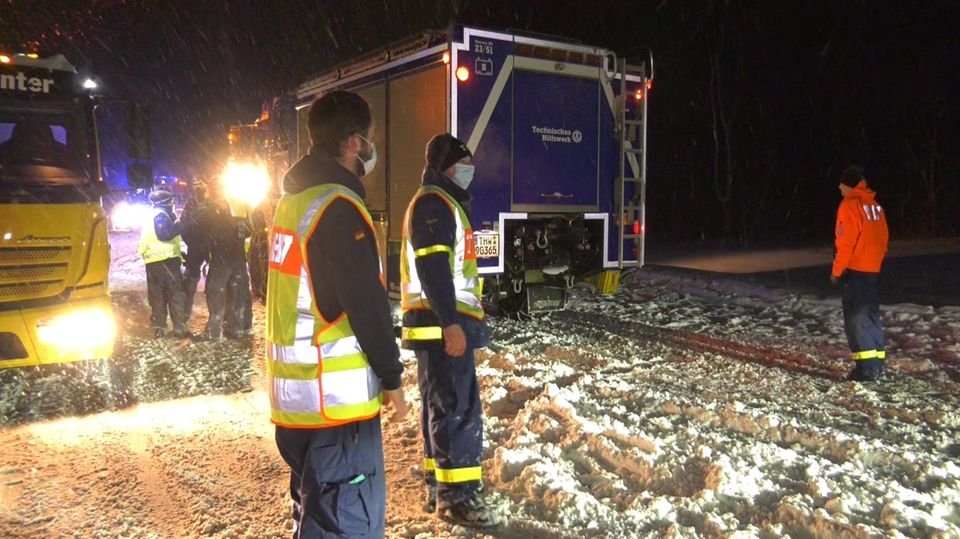 Mitarbeiter des Technischen Hilfswerks stehen während eines Staus auf der Autobahn 2 bei Bielefeld