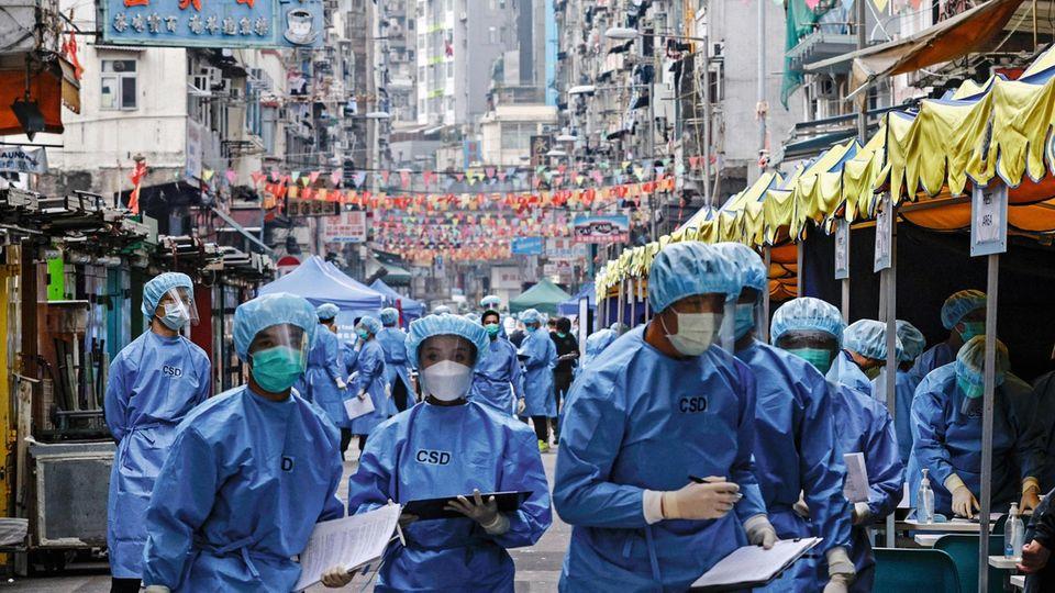 Ausschwärmen in Hongkong: Mitarbeiter der Gesundheitsbehörde versuchen, einen Ausbruch einzudämmen