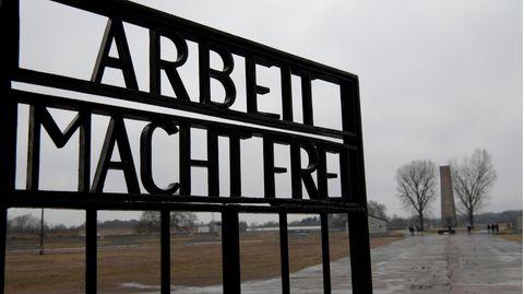 """""""Arbeit macht frei"""" steht am Eingangstor des ehemaligen Konzentrationslagers in der Gedenkstätte Sachsenhausen"""