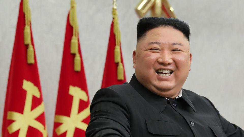 Kim Jong Un - ein übergewichtiger Asiate mit rundem Kopf und schwarzem Bürstenschnitt - steht an einem Rednerpult und lacht