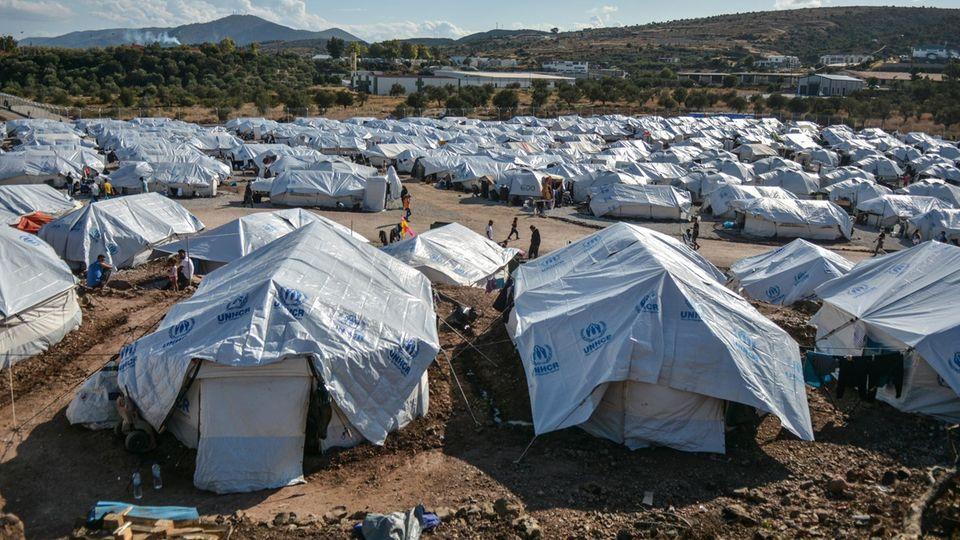 "Migranten gehen nach starken Regenfällen durch das Flüchtlingslager ""Kara Tepe"""