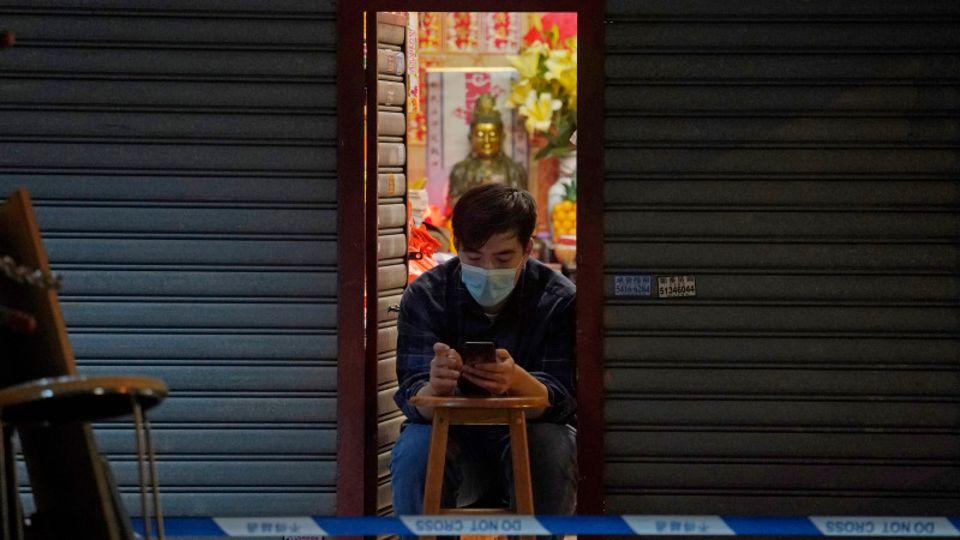 Ein Mann benutzt sein Smartphone im Eingang eines Geschäftes.