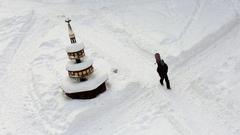 Ein Passant geht mit einem Snowboard über den Marktplatz von Wernigerode mit dem tiefverschneiten Marktbrunnen in Sachsen-Anhalt.