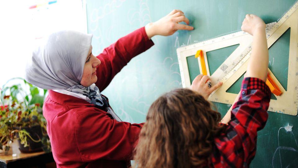 Eine Lehrerin mit Kopftuch steht mit einem Schüler an der Tafel
