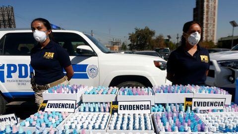 Polizistinnen mit Masken stehen neben beschlagnahmten Flaschen mit Alkohol-Gel, die ohne Genehmigung verkauft wurden