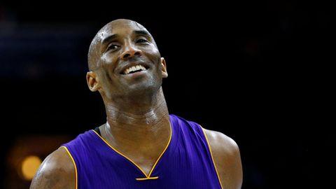 """Ein kahlköpfiger Schwarzer steht in lila """"Lakers""""-Basketballtrikot lächelnd auf dem Spielfeld einer Sporthalle"""