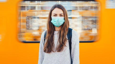 Coronavirus: Eine Frau mit Maske steht vor einer U-Bahn