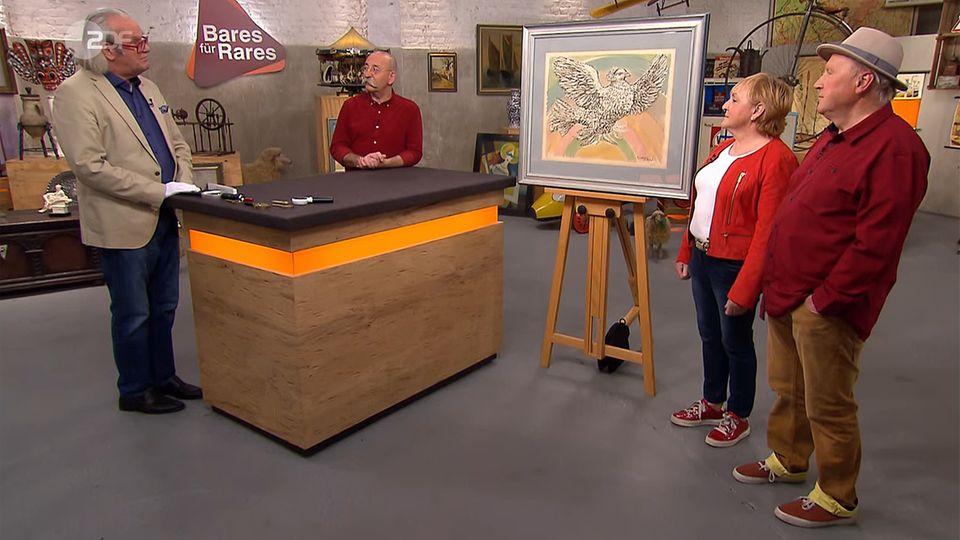 """""""Bares für Rares""""-Experte Albert Maier erklärt in der ZDF-Trödelshow die Herkunft des Picasso-Bildes. Moderator Horst Lichter und das Besitzer-Ehepaar Franke hören zu."""
