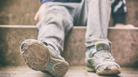 Kind mit kaputten Schuhen