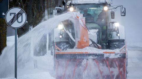 Eine Schneefräse beseitigt Schneeverwehungen auf einer Straße im Norden der Insel Rügen