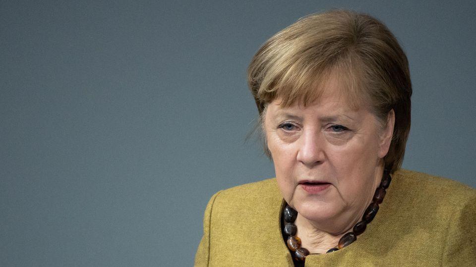 In einem grüngelben Blazer steht Kanzlerin Merkel am Rednerpult des Bundestags und gestikuliert beim Sprechen mit rechter Hand