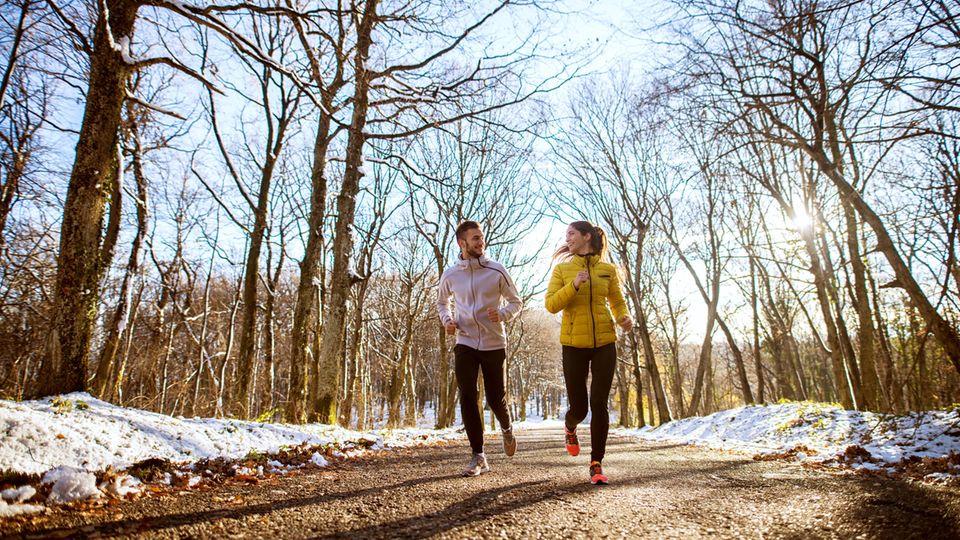 Jogging Outfit: Pärchen läuft auf einem Waldweg und schaut sich dabei an