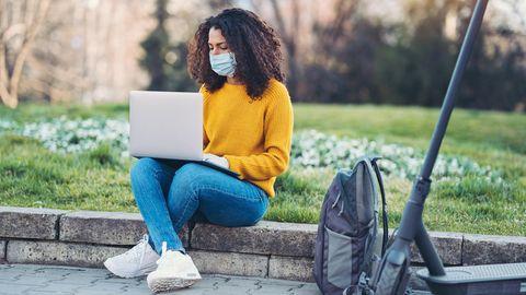 Junge Frau mit OP-Maske sitzt miz ihrem Laptop auf einer Wiese, neben ihr steht ein Tretroller.