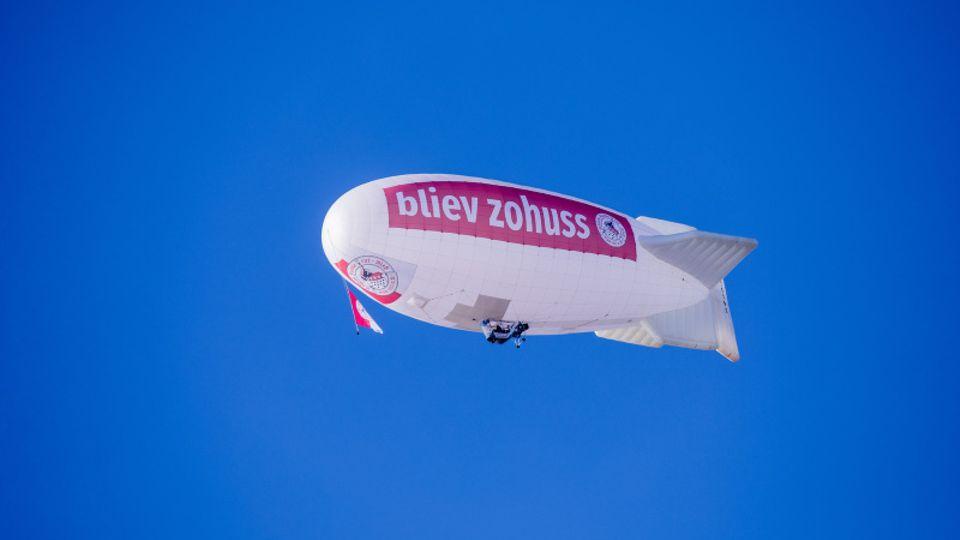 Ein Zeppelin mit der Aufschrift «bliev zohuss» vom Karnevalscorps Rote Funken fliegt über die Kölner Altstadt.